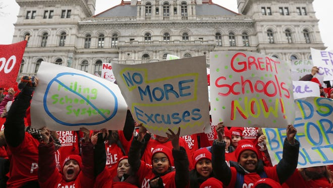 Students hold signs during a charter school rally outside the state Capitol on Wednesday, March 4, 2015, in Albany, N.Y. (AP Photo/Mike Groll)