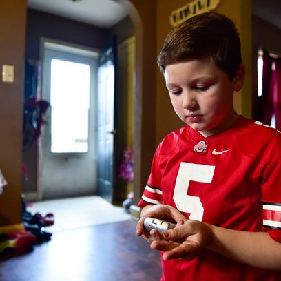 Seven-year-old Luke Trippett, tests his blood sugar
