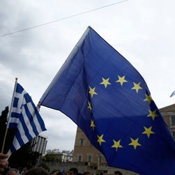 A demonstrator holds a European Union and Greek flag during a rally on June 30, 2015, in Athens.