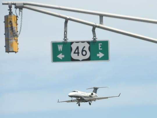 A plane flies over Route 46 as it approaches Teterboro