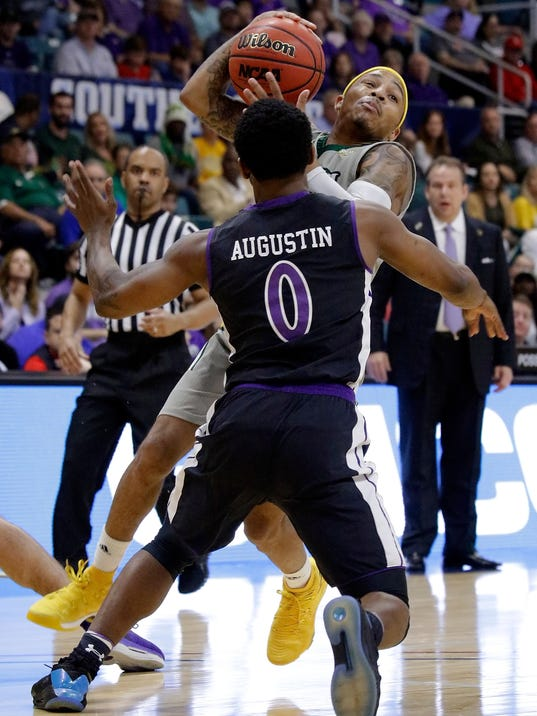 Southeastern Louisiana guard Marlain Veal (0) looks to drive around Stephen F. Austin guard Aaron Augustin (0) during the first half of an NCAA college basketball game in the Southland Conference's Men's Basketball Tournament Championship Saturday, March 10, 2018, in Houston. (AP Photo/Michael Wyke)