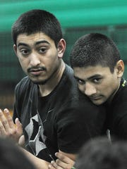 Assistant wrestling coach Samuel Rodriguez, left, and his brother Andrew Rodriguez, practice a technique at a Pacifica High wrestling practice.