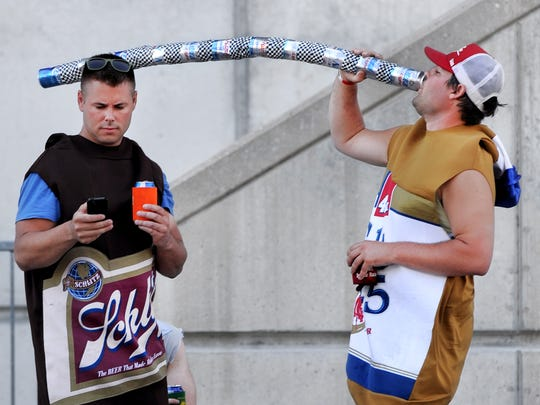 Daniel DeVore of Oklahoma takes a drink while he and friend Dave Reinhart, Jeffersonville, Ind., wear their best race outfits at the 2013 edition of Carb Day.