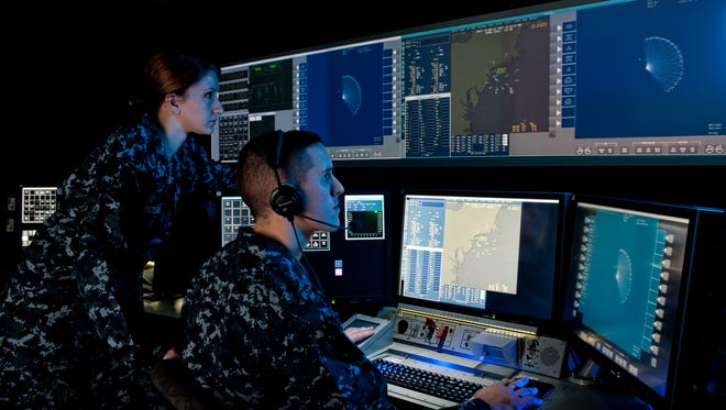 Sailors  operate consoles and view computer screens in a replicated ship combat center at the expanded Lockheed Martin/Navy site in Moorestown. They learn how to operate and test Aegis weapons systems  used in the  dimly lit combat centers of cruisers and destroyers.