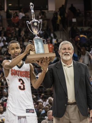 Southside senior point guard Jalen McKelvey, left, and Tigers coach Steve Beasley hold aloft the state championship trophy after Southside defeated Dillon 65-57 in the Class AAA final March 4 in Columbia.