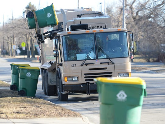 A Green Bay trash collection truck works on a row of