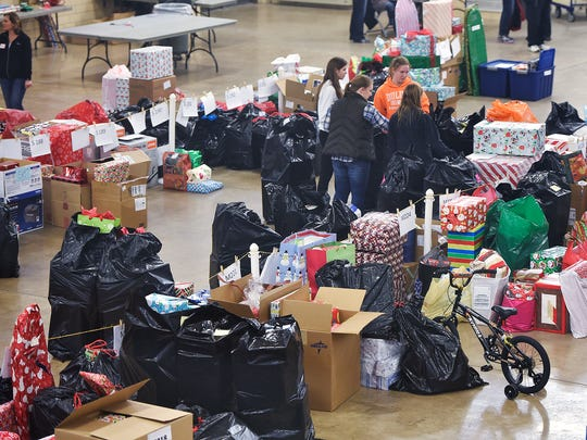 Wrapped gifts for the Share the Spirit event fill the floor of the St. Cloud Armory in December 2015.
