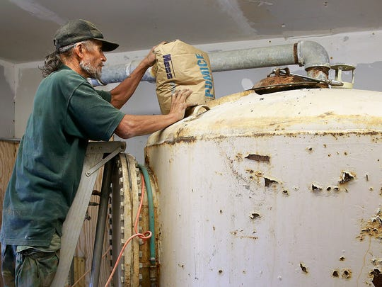 AV Water employee Joe Moya adds pumice to a filtration system in the Harvest Gold water system on Tuesday east of Bloomfield.