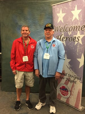Kevin Schaack and Spencer Smith pose for a photo next to the welcome banner for the Stars and Stripes Honor Flight Oct. 14.