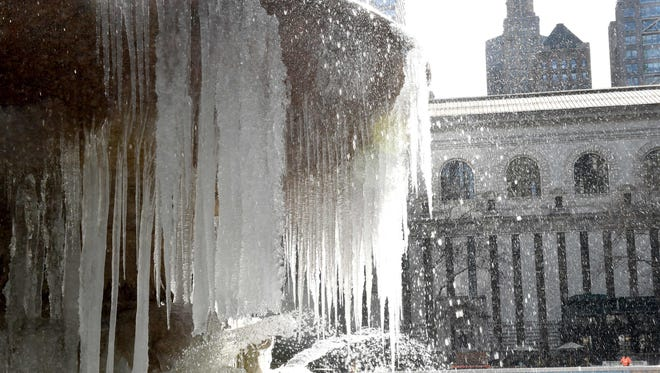 The Josephine Shaw Lowell Memorial Fountain in Bryant Park is covered in ice and snow as Winter Storm Stella pounds the East Coast.