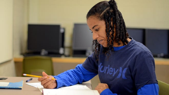 Shamila Torres works on a placement test Monday, Aug 24, 2015, during registration at the Harrison Education Center in Port Huron.