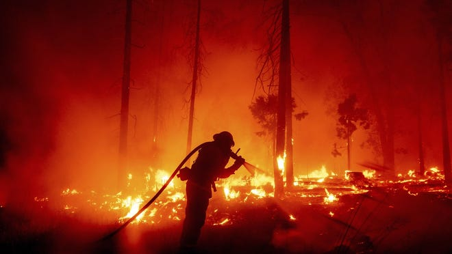 In this Sept. 7  file photo, a firefighter battles the Creek Fire as it threatens homes in the Cascadel Woods neighborhood of Madera County, Calif.