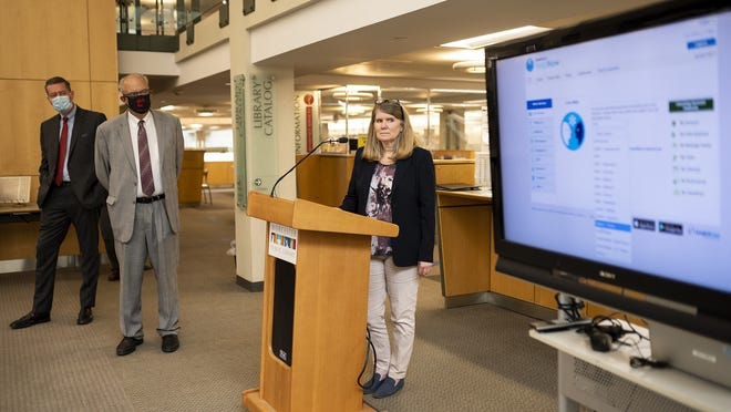Cynthia Bermudez, youth services coordinator at the Worcester Public Library, shows off an online tutoring program for students, available free with a library card. At left are City Manager Edward Augustus and Mayor Joe Petty.