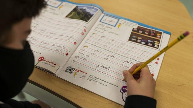 Fourth-grader Graham Binnick practices in a cursive workbook at Hildreth Elementary School in Harvard.