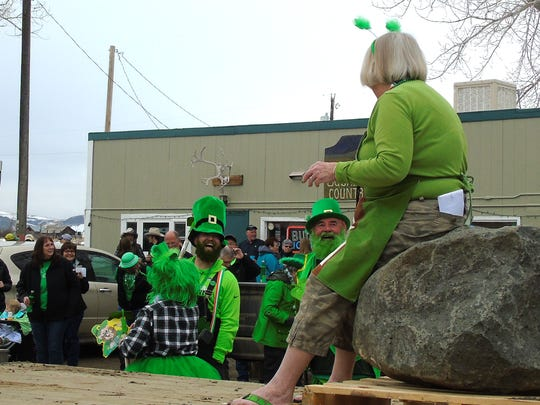 Cynthia Lenington, mayoral candidate, rides on a boulder in the Square Butte St. Patrick's Day Parade.