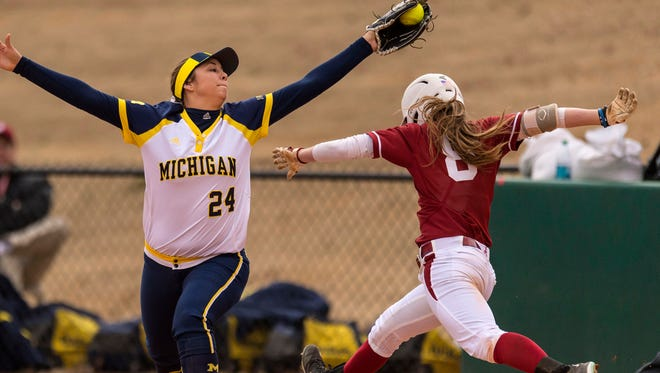 Michigan's Tera Blanco (24) gets Alabama outfielder Haylie McCleney (8) on a bunt attempt on Feb. 21 at Rhoads Stadium in Tuscaloosa, Ala.