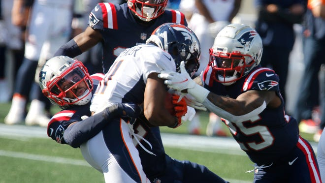 New England's Adrian Phillips, left, and Terrence Brooks combine to take down Denver running back Diontae Spencer in the first half of Sunday's game at Gillette Stadium.