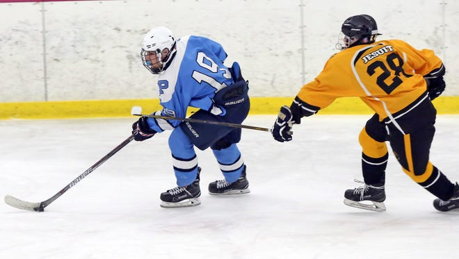Stefan Mikiakos (19) of Pelham keeps the puck away from Ryan McEvily (28) of McQuaid during the Great 8 Plus 1 Ice hockey tournament at the Ice Hutch in Mount Vernon Dec. 9, 2016.