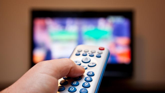 watching tv. Remote control in hand.