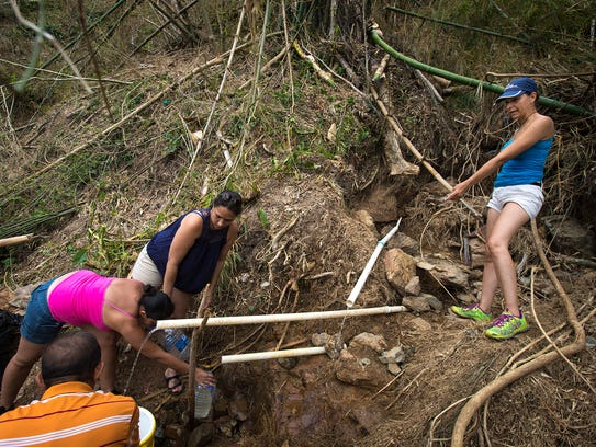 USA TODAY first met Michelle Rebollo, right, about a week after Hurricane Maria struck the island as she was collecting water from a stream on the side of a mountain outside of Naranjito, Puerto Rico.