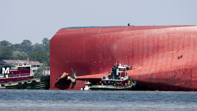 Rescuers work near the stern of the vessel Golden Ray as it lays on its side near the Moran tug boat Dorothy Moran, Monday, Sept. 9, 2019, in Jekyll Island, Ga. Coast Guard rescuers have made contact with four South Korean crew members trapped inside the massive cargo ship off the coast of Georgia.