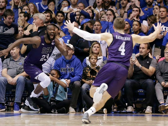 Stephen F. Austin forward Nathan Bain (23) and guard David Kachelries (4) celebrate Bain's game winning basket against Duke in overtime of an NCAA college basketball game in Durham, N.C., Tuesday, Nov. 26, 2019. (AP Photo/Gerry Broome) ORG XMIT: NCGB111