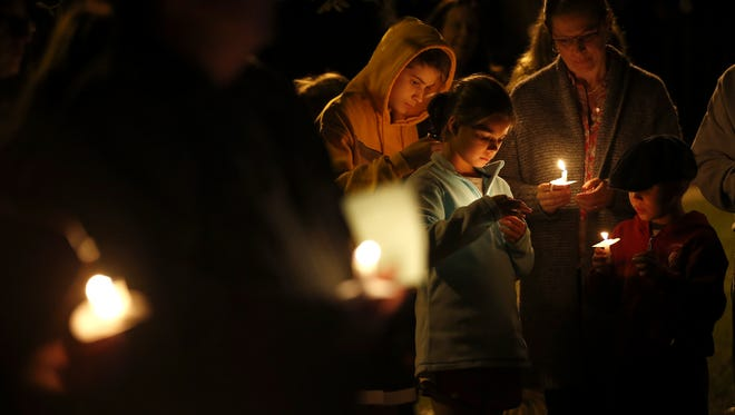 People hold candles in honor of victims of the recent terrorist attacks in Paris during a vigil held at Lake Ella on Sunday.