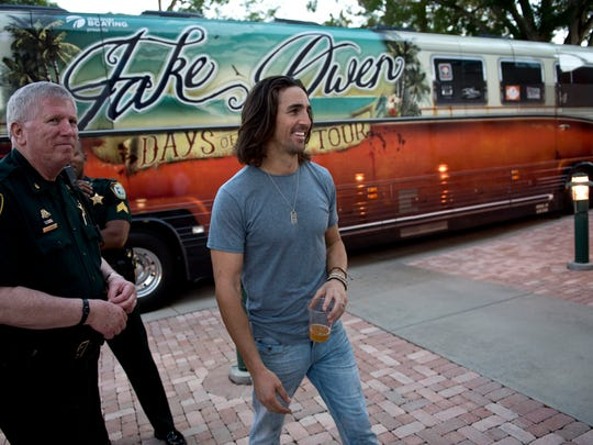 Country musician Jake Owen (right) walks past Jeff Luther of the Indian River County Sheriff's Office as he goes to meet fans prior to his concert at Historic Dodgertown on Saturday night.