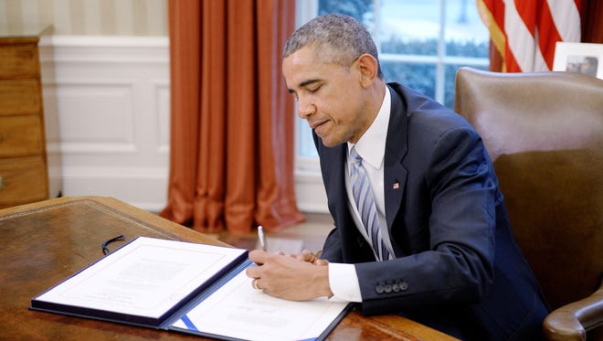President Obama signs the Department of Homeland Security funding bill in the Oval Office of the White House March 4, 2015.