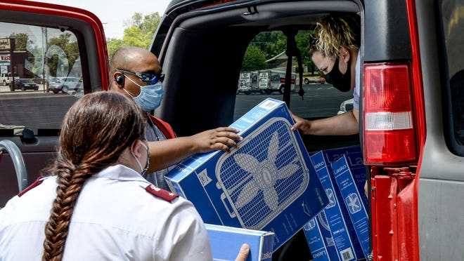 Westlake Ace Hardware sales associate Davon Beach, center, helped Salvation Army workers Chelsea Barnes, left, and Sabrina Maldonado, right, load 22 donated fans into the Salvation Army's van on Thursday. The fans will be given out to people in need in the community.