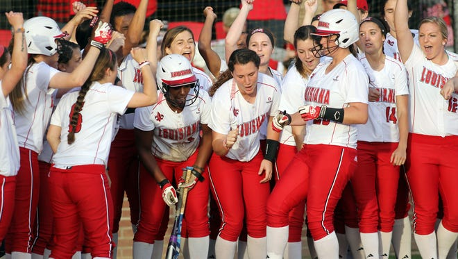 UL senior Shellie Landry, center, is one of many teammates greeting fellow senior Kelsey Vincent (28) at the plate during a home run earlier. Landry and Vincent join Sara Corbello as senior regulars playing their final regular season home series this weekend at Lamson Park.