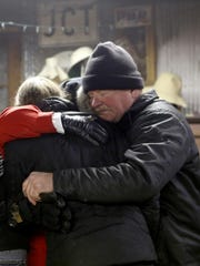 Duane Doyle hugs Ruby Young after a fire Sunday, Feb. 14, 2016.