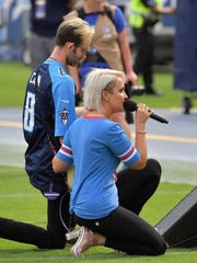 Meghan Linsey kneels after singing the national anthem