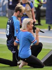 Meghan Linsey kneels after singing the national anthem