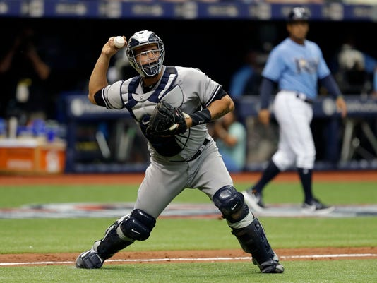 New York Yankees catcher Gary Sanchez throws the ball wide of first base for an error on a bunt by Tampa Bay Rays' Mallex Smith during the third inning of a baseball game Sunday, April 2, 2017, in St. Petersburg, Fla. Tim Beckham scored. (AP Photo/Chris O'Meara)