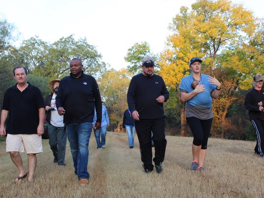 Early morning sunlight strikes fall color as Mayor Anthony Williams and Richard Rodgers, the city of Abilene's Parks Division manager, lead hikes along Cedar Creek. One hike was Elaine Singiser, carrying her baby daughter of six weeks, Penelope.