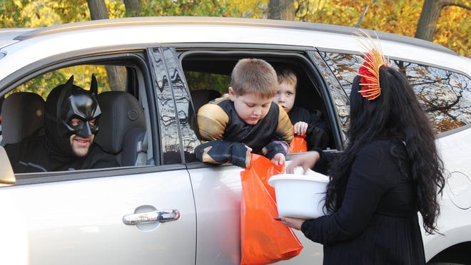 A couple of children receive some candy as Batman looks on during the Fun Fest at Chautauqua Park last weekend. The event included drive-thru trick-or-treating.