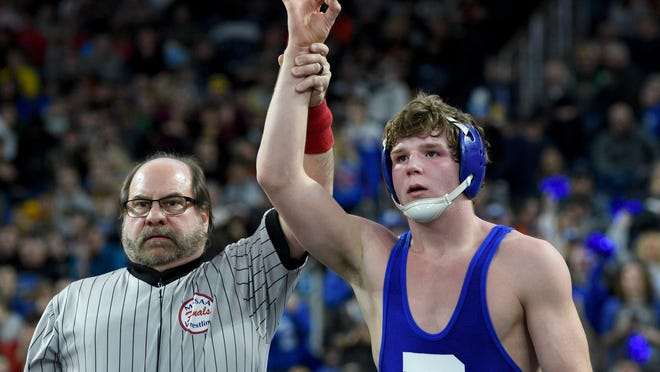 Stoney Buell of Dundee  puts up three fingers to signal his third state title  after he beat Randy Pyrzewski of Gladwin in the Division 3 state finals at 160 pounds in March.