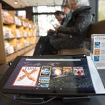 Customers can try out Amazon products, like reading magazines on their Fire tablet, at the new Amazon Books store at University Village in Seattle, Washington on November 3, 2015.  Twenty years after pioneering the virtual bookstore, Amazon went brick-and-mortar.   The online giant, which led the bookselling industry's shift to the Internet, opened its first physical bookstore in its hometown of Seattle, Washington.