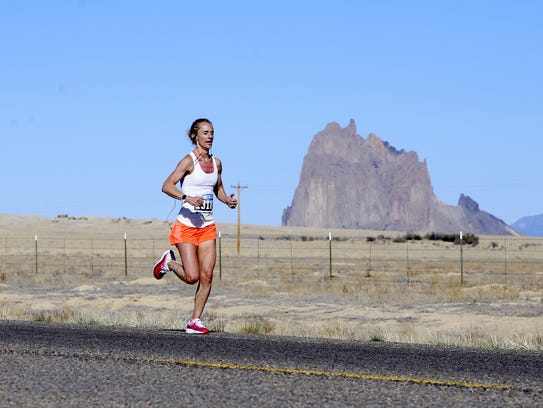 Farmington resident Christi Webb runs past the Shiprock pinnacle Saturday during the Shiprock Half Marathon. Webb was the first female to cross the finish line in the half marathon race.