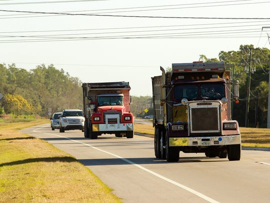 Dump trucks carrying sand to a Collier County beach renourishment project travel on Corkscrew Road on Thursday, Nov. 14, 2013, in Estero.