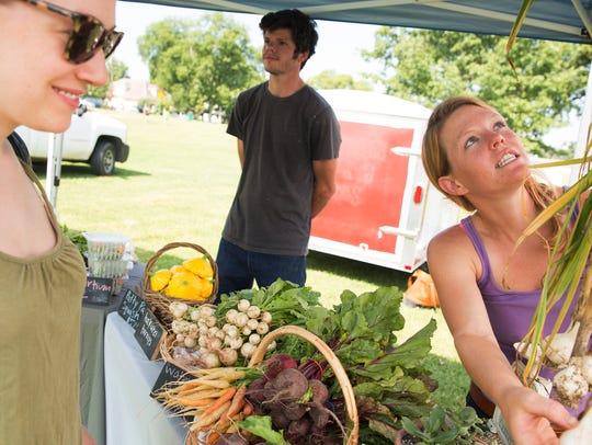 Jessica Moog examines produce with Sounding Stone Farm
