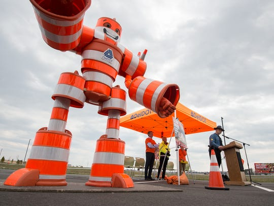 Sgt. Richard Bratz, public relations officer with the Delaware State Police, gives his remarks next to Wally the Work Zone Warrior at the work zone safety awareness ceremony at DE Turf Sports Complex near Frederica.