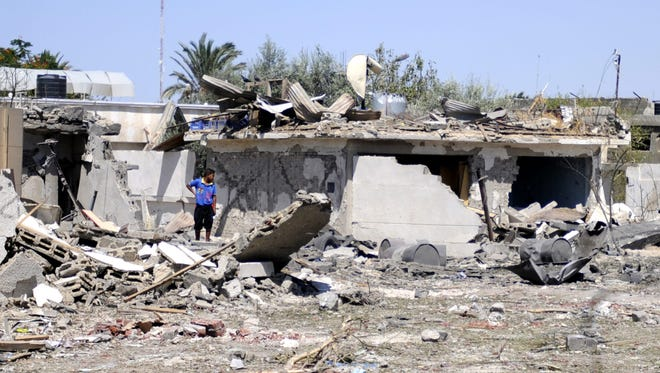A man stands amid the rubble of a damaged building near the site of an explosion Sept. 11, 2013, that was targeting a military headquarters in Rafah, Egypt. Six soldiers were killed and 17 people were injured, including seven civilians, in the town of Rafah, according to reports.