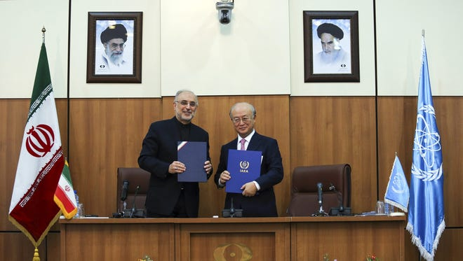 Ali Akbar Salehi, Iran's nuclear chief, and Yukiya Amano, head of the United Nations' International Atomic Energy Agency, reach a deal Monday in Tehran to allow expanded monitoring of Iranian sites.