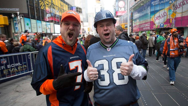 "Denver Broncos fan Nathan Wilkes, left, and Seattle Seahawks fan Jim Rudd, both of Seattle, pose for photos on ""Super Bowl Boulevard"" at Times Square in New York on Saturday."