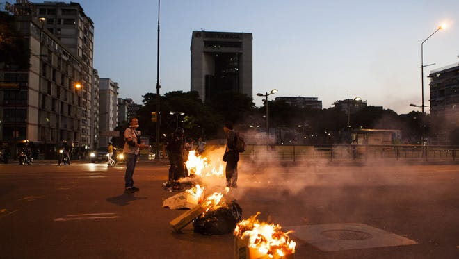 A group of demonstrators burn garbage at Altamira square in Caracas, Venezuela, on Feb. 12, 2014.