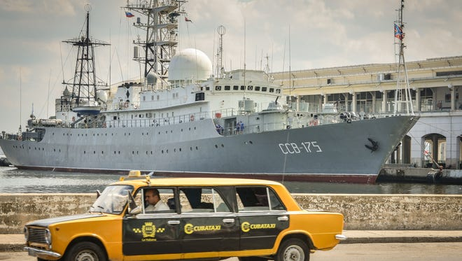A  Soviet-made Lada limousine passes by the Russian warship Viktor Leonov, which docked Feb. 26, 2014, in Havana harbor. The  1980s-era Vishnya-class ships are used for gathering intelligence.