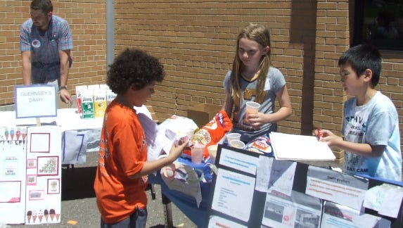Third-grader Nikki Schade (center) is ready with a sample of potato chips as Shunta Manabe (right) asks a visitor to sign in at their display on tourist attractions during Thursday's Michigan economics fair at Amerman Elementary.