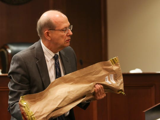 District Attorney Art Bieber brings up a bat used as